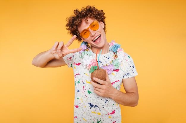 Chico atractivo feliz en gafas de sol con cóctel de coco