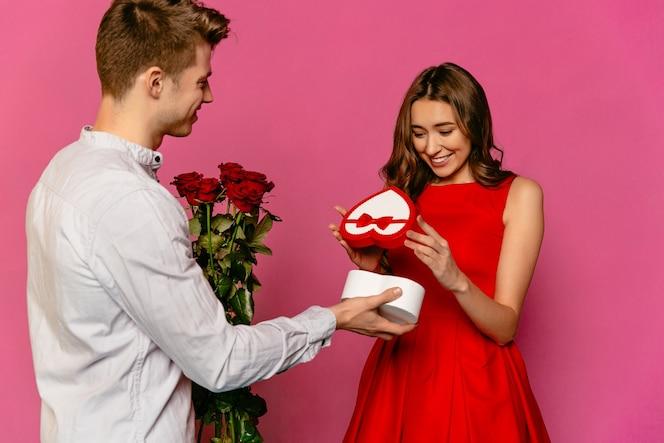 Chico atractivo haciendo regalos regalo en forma de corazón