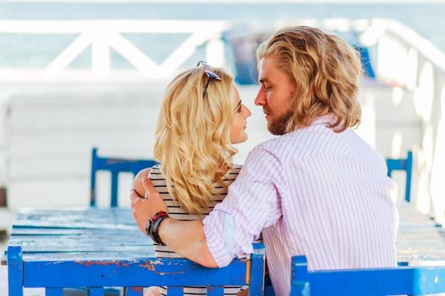 Chico atractivo y hermosa mujer rubia tener una cita sentados en sillas azules en un café de playa retro y disfrutar del verano