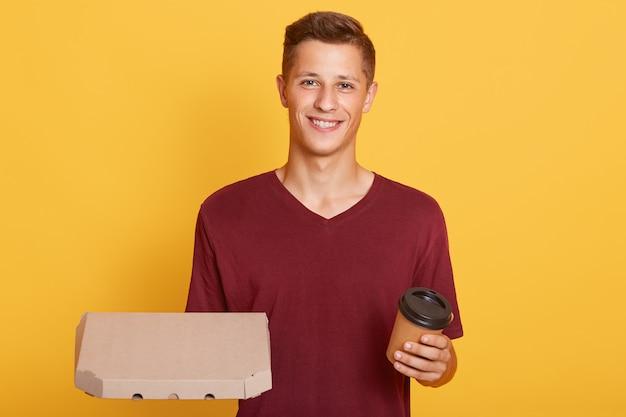 Chico atractivo con llevar café y caja de cartón con pizza