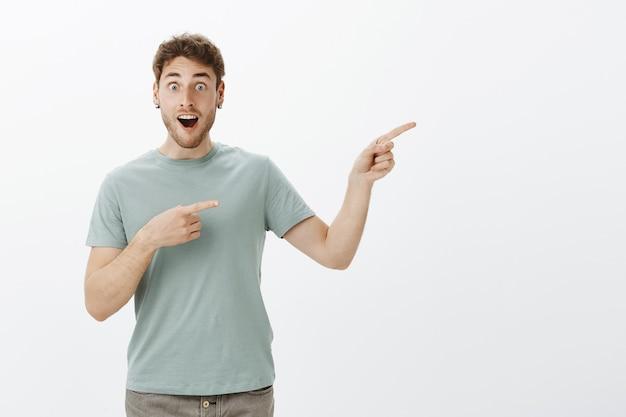 Chico atractivo sorprendido complacido con cabello rubio, con la mandíbula caída mientras habla de algo increíble, apuntando a la derecha con los dedos índices, jadeando de alegría y emoción.