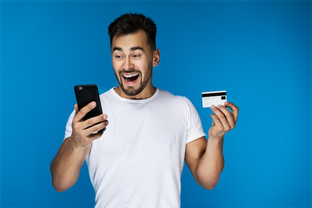 Chico atractivo sorprendido está mirando en el teléfono celular y con tarjeta de crédito