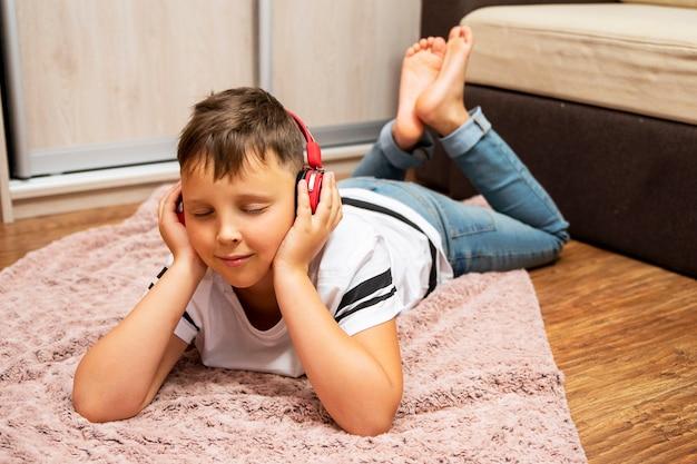 Chico en auriculares escuchando música. está acostado cerca del sofá. está meditando y disfrutando.