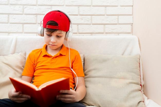 Chico con auriculares leyendo