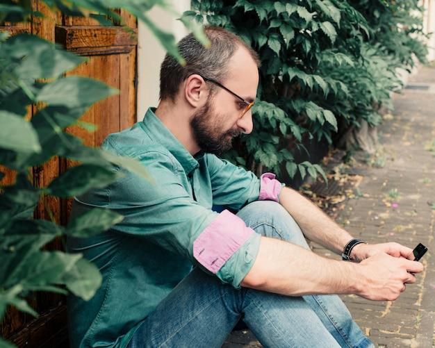 Chico barba gafas hombre de la calle usa el teléfono den haag la haya sity walk one