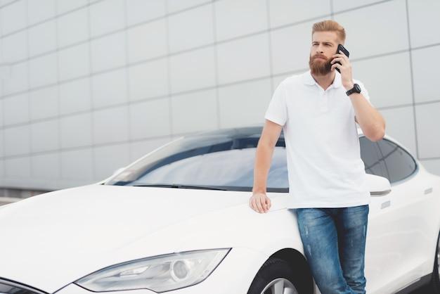Chico con barba hablando por teléfono cerca de su coche eléctrico.