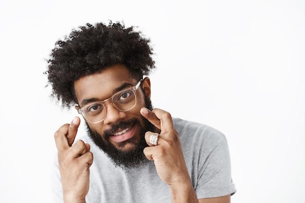 Chico barbudo afroamericano optimista y alegre con peinado afro y gafas dobladas mientras cruzan los dedos para desear suerte sonriendo alegremente soñando con orar hecho realidad sobre una pared gris