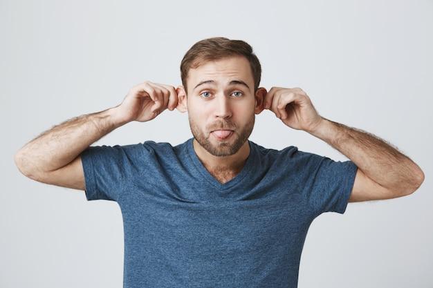 Chico barbudo despreocupado divertido que tira de las orejas y muestra la lengua tonta, simulando