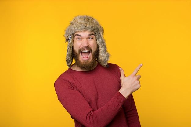 Chico barbudo en divertido sombrero de invierno, gritando y apuntando hacia arriba sobre fondo aislado