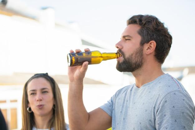 Chico barbudo enfocado disfrutando de cerveza con amigos