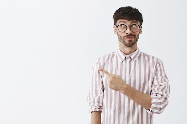 Chico barbudo con estilo curioso posando contra la pared blanca con gafas