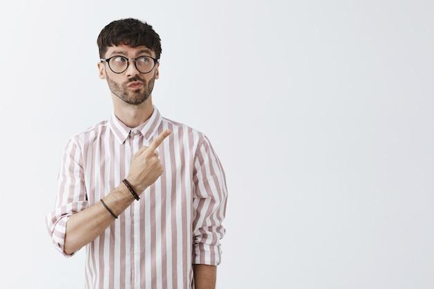Chico barbudo con estilo inseguro posando contra la pared blanca con gafas