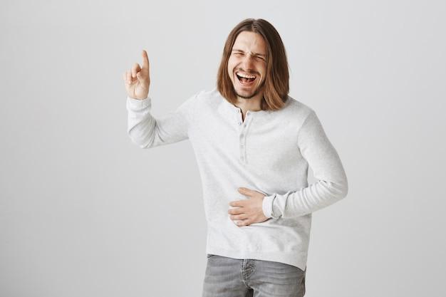 Chico barbudo feliz riendo en promo divertida, apuntando hacia el anuncio