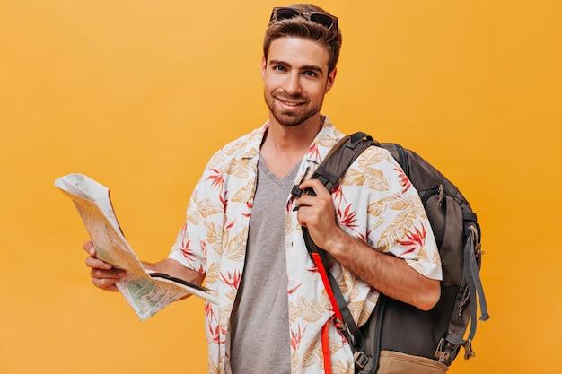 Chico barbudo sonriente en camisa ligera de verano y camiseta lisa posando con mochila y mapa y mirando a cámara y pared naranja