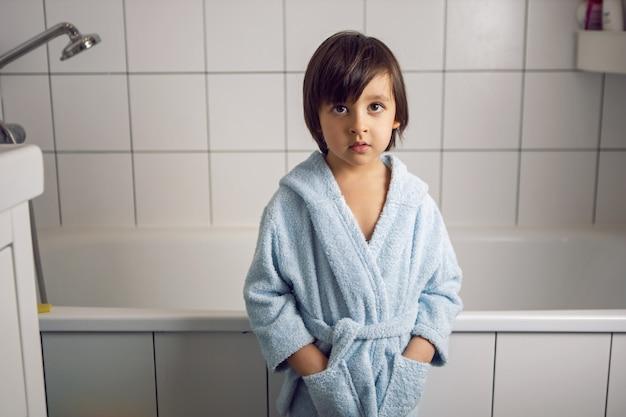 Chico en una bata de baño azul se encuentra en el baño después de un spa