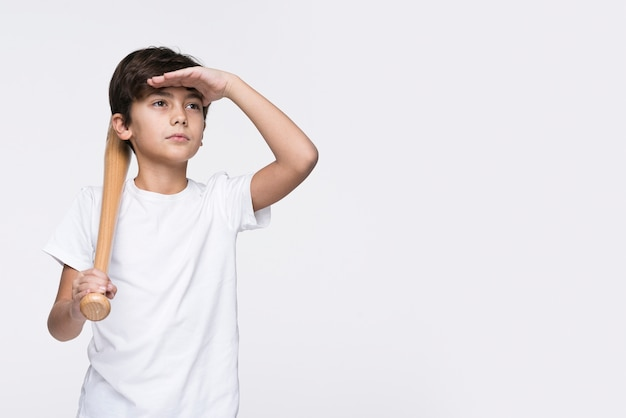 Chico con bate de béisbol mirando a otro lado