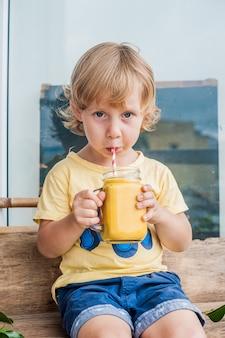 Chico bebiendo jugoso batido de mango en frasco de vidrio con paja roja a rayas sobre fondo de madera vieja