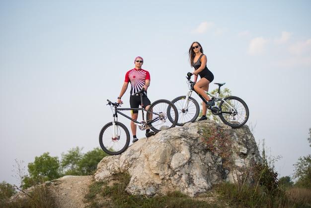 Chico con bicicleta con chica bonita fitness en una bicicleta de montaña de pie sobre una roca