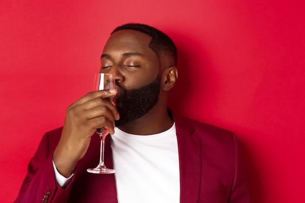 Chico borracho besando copa con champán, celebrando el año nuevo, disfrutando de la fiesta