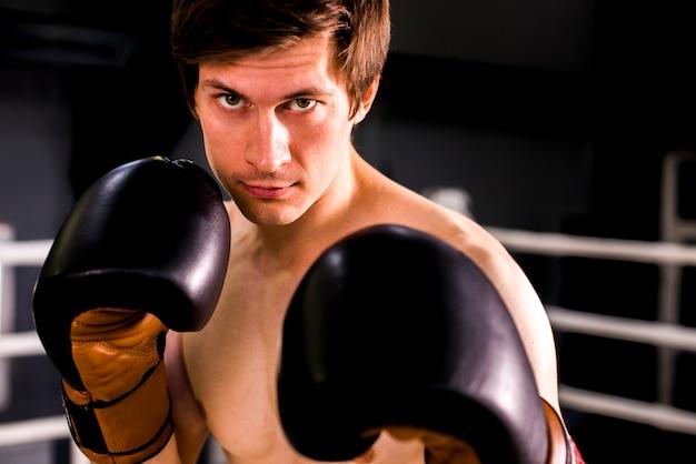 Chico boxeador posando en el gimnasio