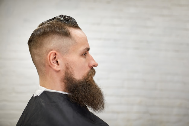 Chico brutal en la moderna peluquería. peluquero hace peinado a un hombre con una larga barba. maestro peluquero hace peinado con cortapelos