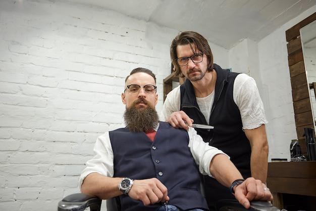Chico brutal en la moderna peluquería. peluquero hace peinado a un hombre con una larga barba. el maestro peluquero hace peinado con tijeras y peine