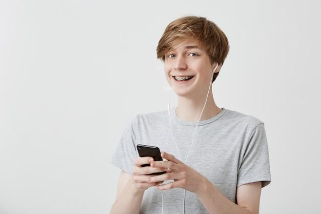 Chico con cabello rubio, vestido con una camiseta gris que sostiene un teléfono inteligente moderno usando una conexión a internet de alta velocidad, enviando mensajes de texto a sus amigos, sonriendo ampliamente. tecnología moderna y comunicación.