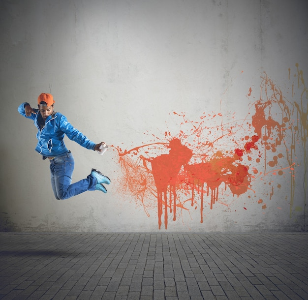 Chico de la calle pintando paredes con spray