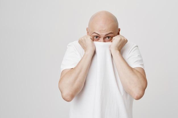 Chico calvo tira del cuello de la camiseta en la cara, escondiéndose y mirando tontamente