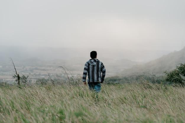 Un chico caminando en el campo a través de la hierba en un sombrío día de niebla