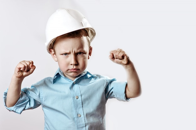 El chico en una camisa ligera y un casco builder muestra cómo es fuerte y confiado
