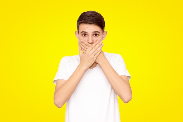 Chico en una camiseta blanca cubre su boca con sus manos, aisladas sobre un fondo amarillo
