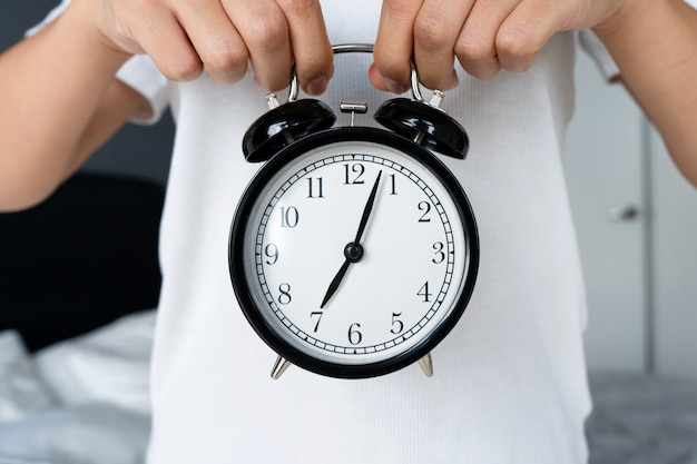 Un chico con una camiseta blanca sostiene un elegante despertador negro con una campana. en el despertador, el comienzo de la octava. hora de levantarse.