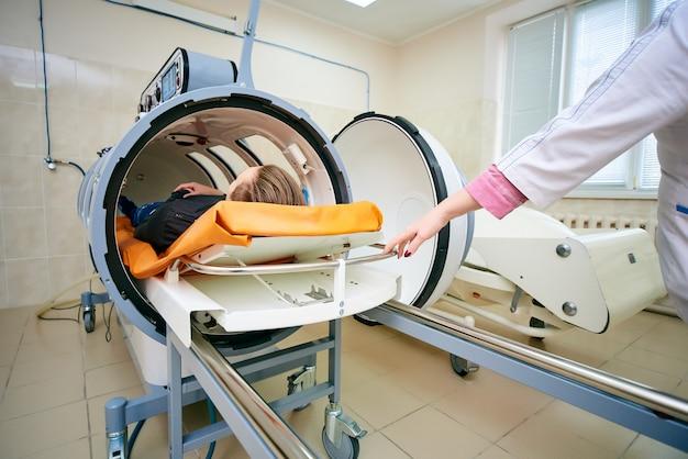 El chico de la camiseta negra yace en la cámara hiperbárica, oxigenoterapia