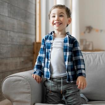 Chico en casa sonriendo y sentado en el sofá