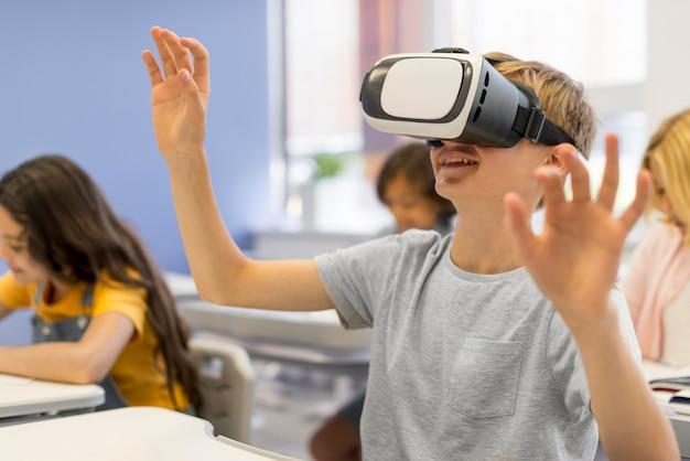 Chico con casco de realidad virtual en la escuela