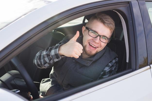 Chico casual alegre sonriendo felizmente mostrando los pulgares para arriba sentado en un gran coche blanco