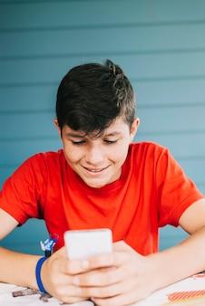 Chico caucásico de 13 años vistiendo una camiseta roja sentado al aire libre usando un dispositivo electrónico