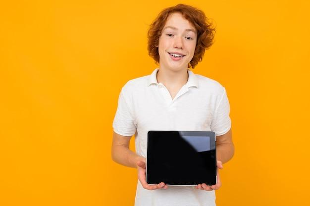 Chico caucásico con una camisa blanca muestra una plantilla de pantalla de tableta en blanco sobre un fondo amarillo con espacio de copia.