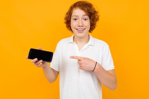 Chico caucásico en una camisa blanca con un teléfono inteligente con una plantilla en blanco sobre un fondo amarillo con espacio de copia