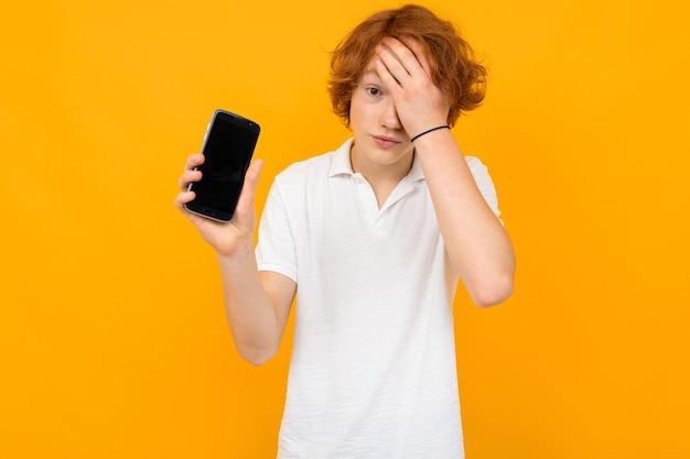 Chico caucásico con una camisa blanca con un teléfono inteligente con una plantilla en blanco sobre un fondo amarillo con espacio de copia.