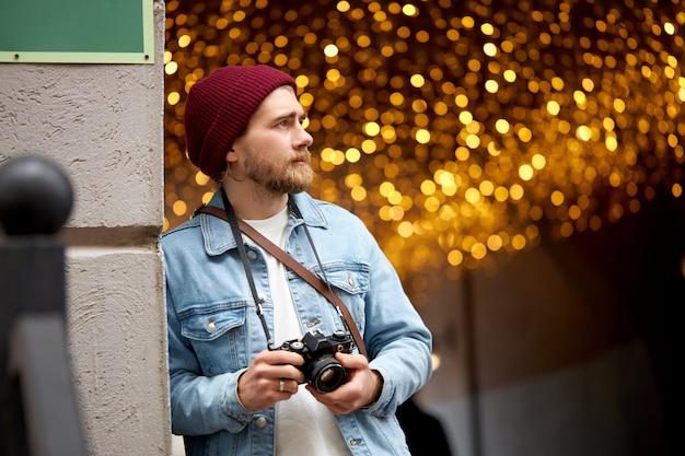 Chico caucásico hipster en chaqueta de mezclilla y sombrero rojo a pie en la calle de la ciudad tomando fotos, usando cámara de película, luces de guirnaldas en el fondo, espacio de copia. fotografía, concepto de estilo de vida de la gente.