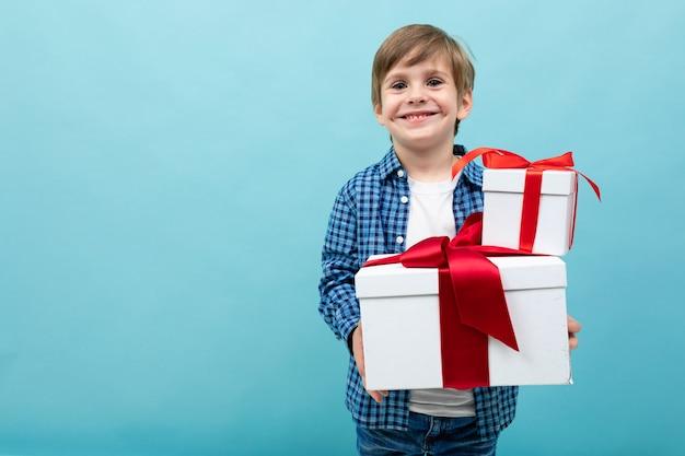 Chico caucásico tiene muchas cajas blancas con regalos y se regocija, retrato aislado en azul