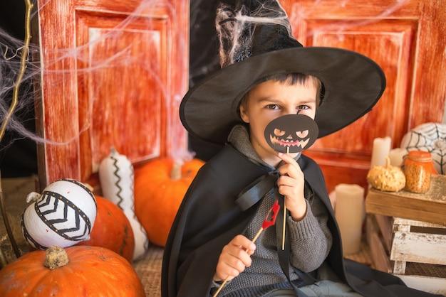 Chico caucásico en traje de mago de carnaval con calabaza de papel negro sobre fondo de decoración de halloween