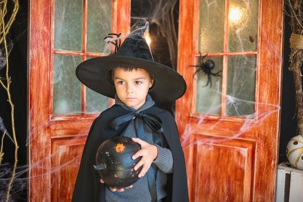 Chico caucásico en traje de mago de carnaval con calabaza pintada de negro sobre fondo de decoración de halloween