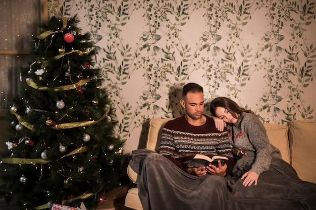 Chico cerca de dama en coverlet con libro cerca de árbol de navidad