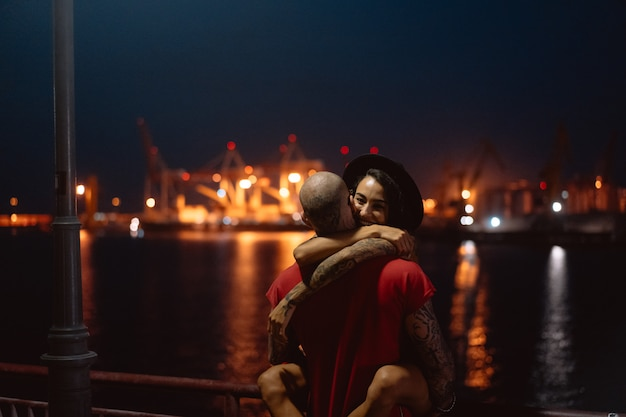Chico y chica abrazándose en un fondo del puerto nocturno