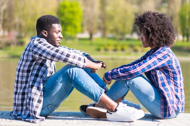 Chico y chica afroamericanos sentados en el suelo con río y bosque