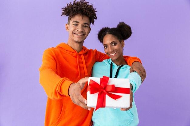 Chico y chica afroamericanos sonriendo mientras sostienen la caja de regalo juntos, aislados sobre la pared violeta