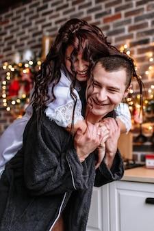 Un chico y una chica en batas en la cocina, que está decorada para la celebración de navidad y año nuevo. la chica se subió a la espalda del chico